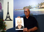 Nelson Faria Marinho shows a picture of his son Nelson Marinho, who lost his life in the 2009 Air France flight 447 accident, during an interview at his home in Rio de Janeiro, Brazil, Thursday, Sept. 5, 2019. French judges dropped a decade-long investigation into Air France and planemaker Airbus over the 2009 crash of a flight from Rio de Janeiro to Paris, which killed all 228 people aboard and led to new aircraft safety regulations. (AP Photo/Silvia Izquierdo)