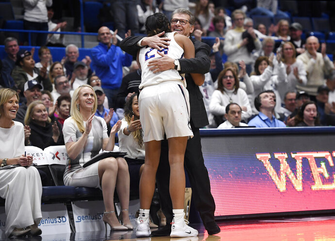 Connecticut head coach Geno Auriemma embraces Connecticut's Napheesa Collier after Collier comes out of the game during the second half of an NCAA college basketball game against South Carolina, Monday, Feb. 11, 2019, in Hartford, Conn. (AP Photo/Jessica Hill)