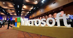 FILE - In this Nov. 30, 2016, file photo a man walks past a Microsoft sign at the annual Microsoft shareholders meeting in Bellevue, Wash. Microsoft on Thursday, Jan. 16, 2020, is announcing a plan to reduce its carbon footprint. (AP Photo/Elaine Thompson, File)