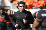 FILE - In this Nov. 2, 2019, file photo, Oklahoma State coach Mike Gundy runs onto the field before the team's NCAA college football game against TCU in Stillwater, Okla. Hubbard said on Twitter that he won't do anything with the program until there is change after Gundy was photographed wearing a T-shirt representing far-right online publication One America News Network. Gundy is seen in a photograph on Twitter wearing the T-shirt with the letters OAN. (AP Photo/Sue Ogrocki, File)