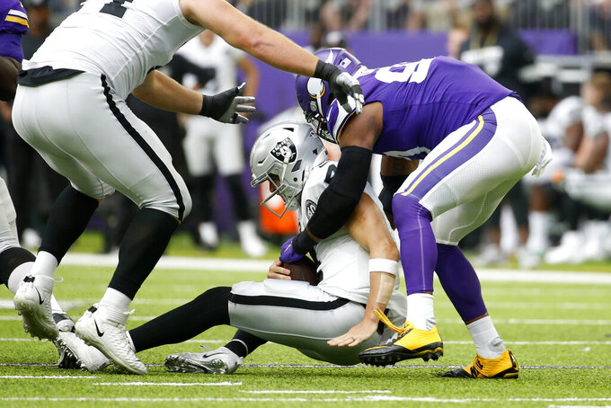 Minnesota Vikings defensive end Everson Griffen, right, sacks Oakland Raiders quarterback Derek Carr during the first half of an NFL football game, Sunday, Sept. 22, 2019, in Minneapolis. (AP Photo/Bruce Kluckhohn)