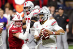 Ohio State quarterback Justin Fields, right, looks for a receiver during the second half of the team's Big Ten championship NCAA college football game against Wisconsin, Saturday, Dec. 7, 2019, in Indianapolis. (AP Photo/AJ Mast)
