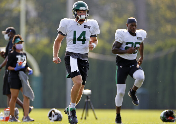 New York Jets quarterback Sam Darnold (14) and running back Le'Veon Bell (26) stretch during a practice at the NFL football team's training camp in Florham Park, N.J., Tuesday, Aug. 25, 2020. (AP Photo/Adam Hunger)