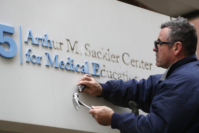 Worker Gabe Ryan removes a sign that includes the name Arthur M. Sackler at an entrance to Tufts School of Medicine, Thursday, Dec. 5, 2019, in Boston. Tufts University says it is stripping the Sackler name from its campus in recognition of the family's connection to the opioid crisis. (AP Photo/Steven Senne)