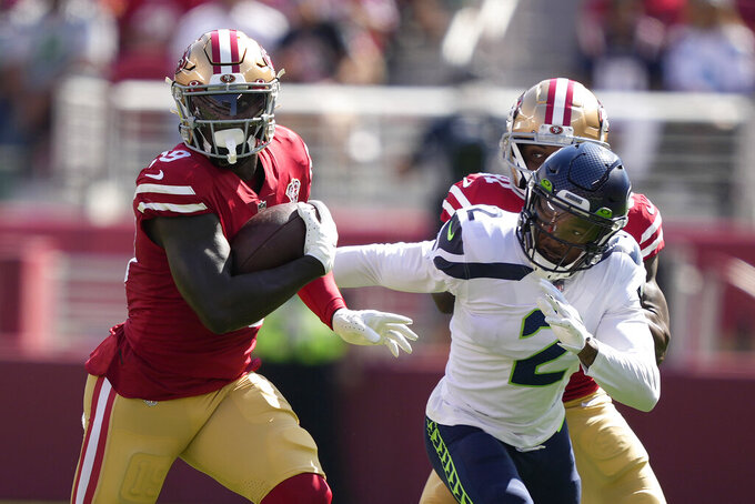 San Francisco 49ers wide receiver Deebo Samuel, left, runs in front of Seattle Seahawks cornerback D.J. Reed (2) during the first half of an NFL football game in Santa Clara, Calif., Sunday, Oct. 3, 2021. (AP Photo/Tony Avelar)