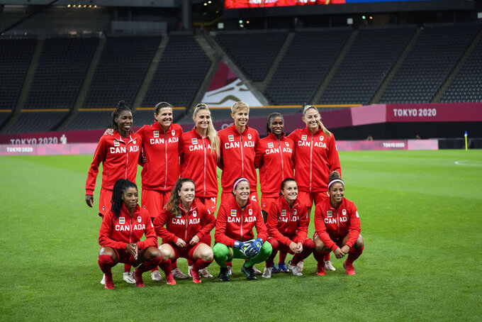 Canada's players pose for a team photo prior during a women's soccer match against Japan at the 2020 Summer Olympics, Wednesday, July 21, 2021, in Sapporo, Japan. (AP Photo/Silvia Izquierdo)
