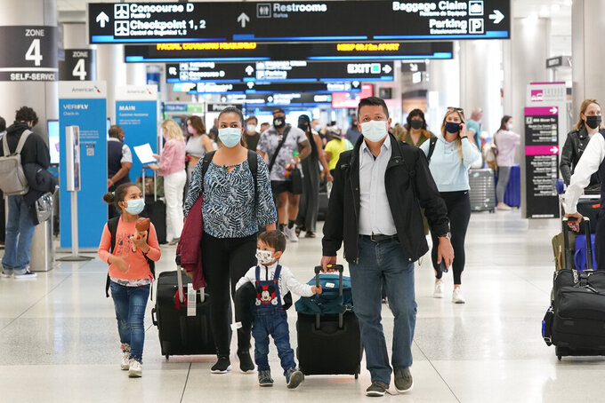 Henry Hernandez, his wife Karina Gonzalez and their children Jose Sebastian, 2, and Laura, 6, of Colombia, walk towards the baggage claim area at Miami International Airport, Friday, May 28, 2021, in Miami. The couple were surprised to be offered the Johnson & Johnson COVID-19 vaccine upon arrival to the U.S. It is their first overseas trip since the pandemic began last year. Florida's Emergency Management Agency is running the program through Sunday.(AP Photo/Marta Lavandier)