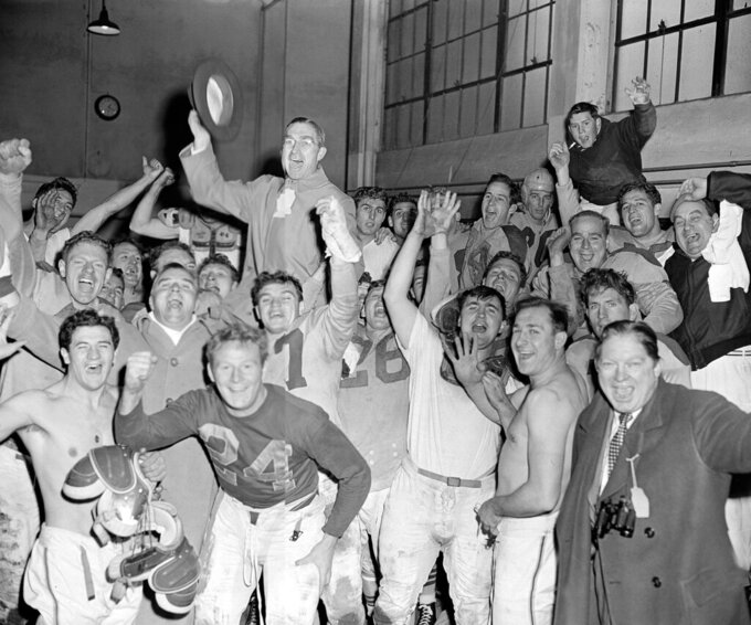 FILE - In this Nov. 22, 1945, file photo, Cleveland Rams football team yell in their dressing room after they beat the Detroit Lions at Detroit to clinch the Western Division championship. Coach Adam Walsh, top, center, waves his hat as he joins in the fun. (AP Photo/Preston Stroup, File)