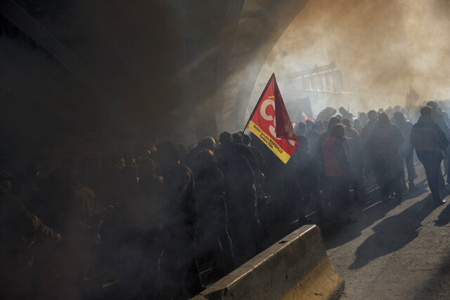 FILE - In this Dec. 10, 2019, file photo, protesters march through smoke from flares at a demonstration during a mass strike in Marseille, southern France. Unions represent less than 10% of salaried workers but have a cozy, if paradoxical, relationship with officialdom that empowers them to block change. (AP Photo/Daniel Cole, File)