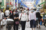 People wearing face masks shop at a mall in Yokohama, near Tokyo, Tuesday, June 23, 2020. Japan's economy is opening cautiously, with social-distancing restrictions amid the coronavirus pandemic. (AP Photo/Koji Sasahara)