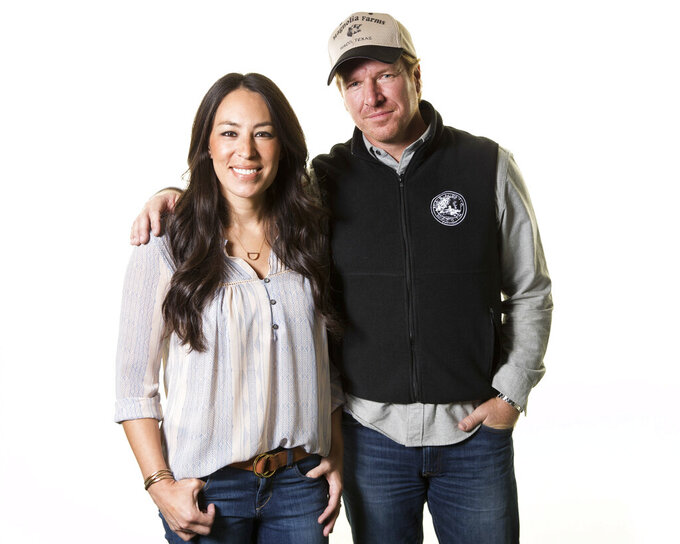 """FILE - In this March 29, 2016 file photo, Joanna Gaines, left, and Chip Gaines pose for a portrait in New York to promote their home improvement show, """"Fixer Upper,"""" on HGTV. The Gaines' Magnolia Network will be blooming late because of the coronavirus crisis. The network's planned October launch is being pushed back because of production delays related to COVID-19 disease, it was announced Tuesday. Discovery Inc.'s DIY Network will be rebranded as the Magnolia Network when the joint venture with the Gaines launches. A new date wasn't immediately announced. (Photo by Brian Ach/Invision/AP, File)"""