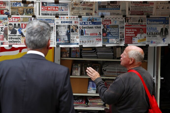 A man reacts as he reads the front pages of Greek newspapers in Athens, Monday, May 27, 2019. Greece's Prime Minister Alexis Tsipras called snap general elections following a resounding defeat of his left-wing Syriza party in European elections. (AP Photo/Thanassis Stavrakis)