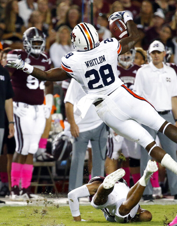 Auburn running back JaTarvious Whitlow (28) is knocked off his feet by a Mississippi State defender as he runs during the first half of their NCAA college football game in Starkville, Miss., Saturday, Oct. 6 2018. (AP Photo/Rogelio V. Solis)