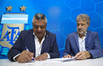 General Secretary of the Argentina's Footballers' Union (FAA) Sergio Marchi, right, Claudio Tapia, president of Argentina's Soccer Federation, left, sign the contract to implement a plan to professionalize women's soccer in Buenos Aires, Argentina, Saturday, March 16, 2019. Almost 90 years after men's soccer turned professional in Argentina, the women's game is still being played by amateur athletes who get little to no money for their work on the field. (AP Photo/Daniel Jayo)