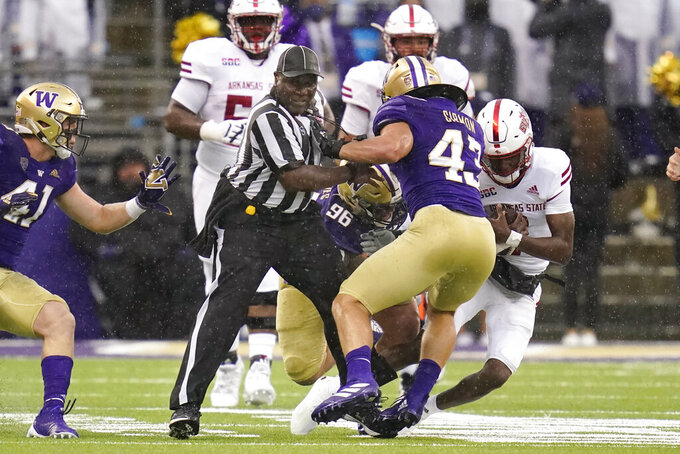 Official Gregory Adams, center, gets caught between players as quarterback James Blackman, right, scrambles against Washington in the first half of an NCAA college football game, Saturday, Sept. 18, 2021, in Seattle. (AP Photo/Elaine Thompson)