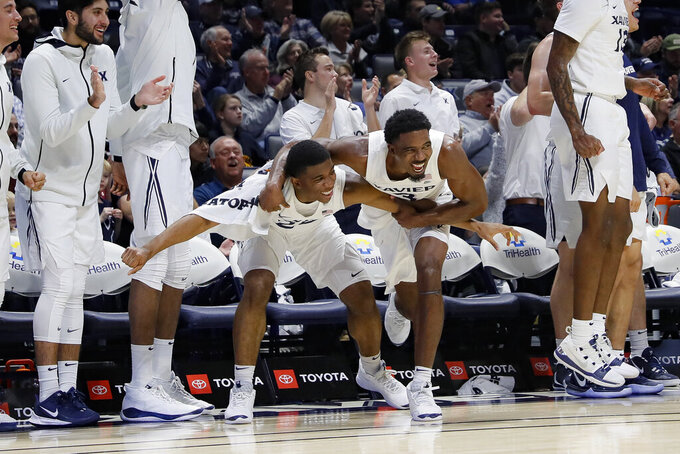 Xavier's KyKy Tandy, center left, and Quentin Goodin, center right, celebrate during the second half of an NCAA college basketball game against Lipscomb, Saturday, Nov. 30, 2019, in Cincinnati. (AP Photo/John Minchillo)