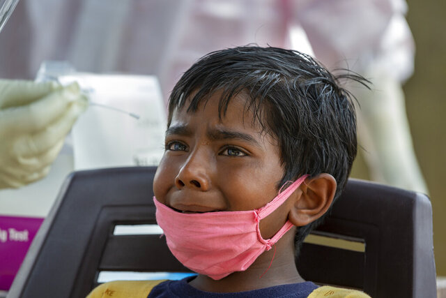 An Indian boy cries as a medical worker prepares to collect his swab sample for COVID-19 test at a rural health centre in Bagli, outskirts of Dharmsala, India, Monday, Sept. 7, 2020. India's coronavirus cases are now the second-highest in the world and only behind the United States. (AP Photo/Ashwini Bhatia)