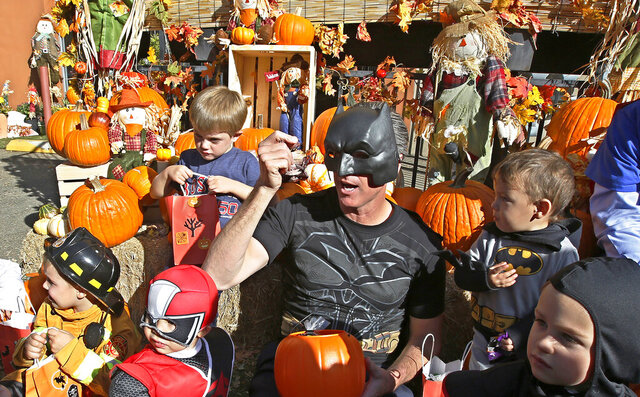 FILE - In this Oct. 31, 2018 file photo, then-Lt. Gov. Gavin Newsom, dressed as Batman, gets into the Halloween spirit as he hands out Halloween treats to costumed children during his visit to The Penleigh Child Development Center in Sacramento, Calif. Halloween traditions, including trick-or-treating, haunted houses and parades, have all been nixed in Los Angeles County in 2020 under new health guidelines because of the coronavirus pandemic. The Department of Public Health says so-called