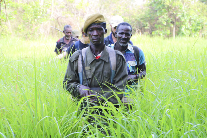 In this photo of Saturday March 16 2019, Rangers walk in a field near the Bire Kpatous game reserve along the Congolese border. South Sudan is trying to rebuild its vast national parks and game reserves following a five-year civil war that killed nearly 400,000 people. The conflict stripped the country of much wildlife but biodiversity remains rich with more than 300 mammal species, including 11 primates, but poaching is a growing threat. (AP Photo Sam Mednick)