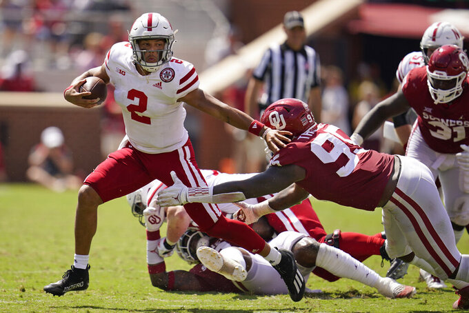 Nebraska quarterback Adrian Martinez (2) carries past Oklahoma defensive lineman Isaiah Thomas (95) in the second half of an NCAA college football game, Saturday, Sept. 18, 2021, in Norman, Okla. (AP Photo/Sue Ogrocki)