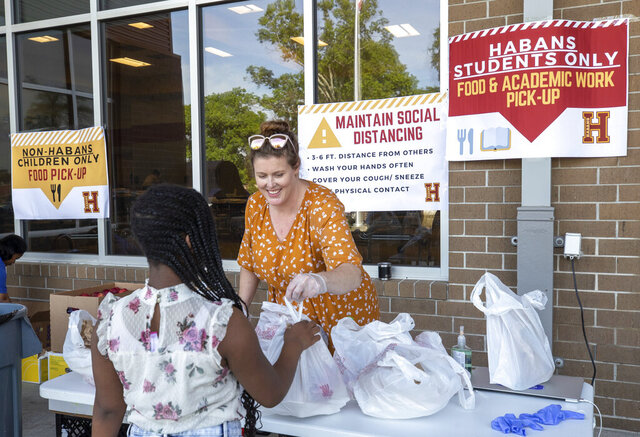 Catie Quinn, operations manager, gives food to a student at Paul Habans Charter School in New Orleans, Monday, March 16, 2020, after public schools closed because of the coronavirus pandemic. (David Grunfeld/The Advocate via AP)