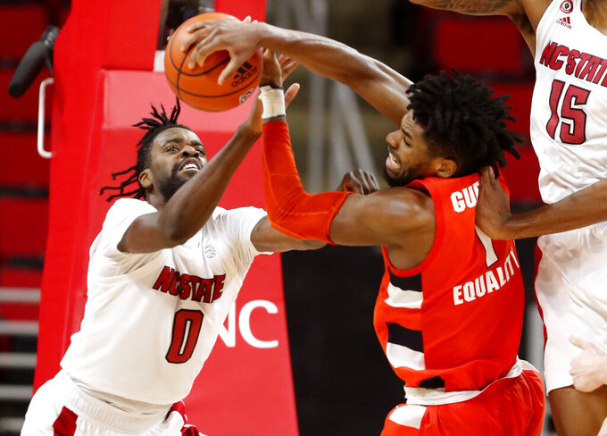 North Carolina State's D.J. Funderburk (0) fights for the rebound with Syracuse's Quincy Guerrier (1) during the second half of an NCAA college basketball game, Tuesday, Feb. 9, 2021 in Raleigh, N.C. (Ethan Hyman/The News & Observer via AP, Pool)