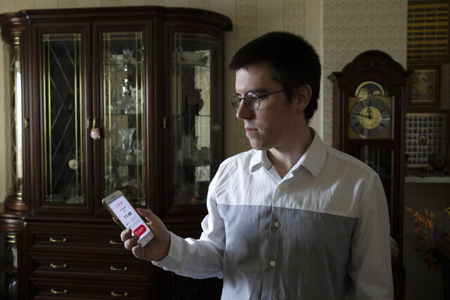In this Wednesday, May 27, 2020, photo, Vladimir Perevalov shows a Social Monitoring app installed on his phone in his apartment in Shcherbinka, outside Moscow, Russia. A smartphone app designed to track Moscow's quarantined coronavirus patients was rolled out by city officials in early April, but complaints about it have mushroomed. Perevalov, who installed the app and diligently took selfies, was fined three times for $168. (AP Photo/Pavel Golovkin)
