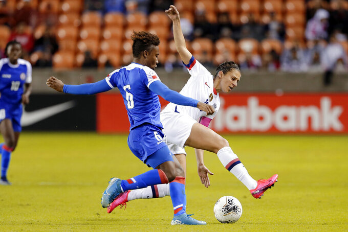 Haiti midfielder Melchie Dumonay (6) tries to move the ball past United States forward Carli Lloyd, right, during the second half of a women's Olympic qualifying soccer match Tuesday, Jan. 28, 2020, in Houston. (AP Photo/Michael Wyke)