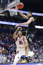 Vanderbilt forward Dylan Disu, top, fouls Arkansas guard Mason Jones (15) in the second half of an NCAA college basketball game in the Southeastern Conference Tournament Wednesday, March 11, 2020, in Nashville, Tenn. Arkansas won 86-73. (AP Photo/Mark Humphrey)