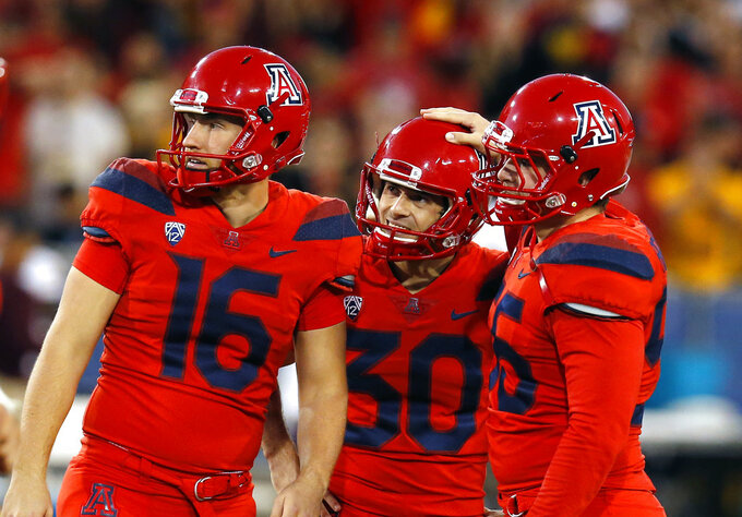 Arizona placekicker Josh Pollack (30) watches with Jake Glatting (16) and Rexx Tessler (55) a missed field goal that would of won an NCAA college football game against Arizona State, Saturday, Nov. 24, 2018, in Tucson, Ariz. Arizona State defeated Arizona to claim the Territorial Cup. (AP Photo/Rick Scuteri)