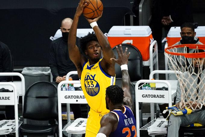 Golden State Warriors center James Wiseman (33) shoots over Phoenix Suns center Deandre Ayton during the first half of an NBA basketball game, Thursday, March 4, 2021, in Phoenix. (AP Photo/Rick Scuteri)