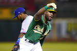 Oakland Athletics' Starling Marte gestures toward teammates after hitting an RBI triple, next to Texas Rangers' Yonny Hernandez during the fourth inning of a baseball game in Oakland, Calif., Friday, Sept. 10, 2021. (AP Photo/Jeff Chiu)