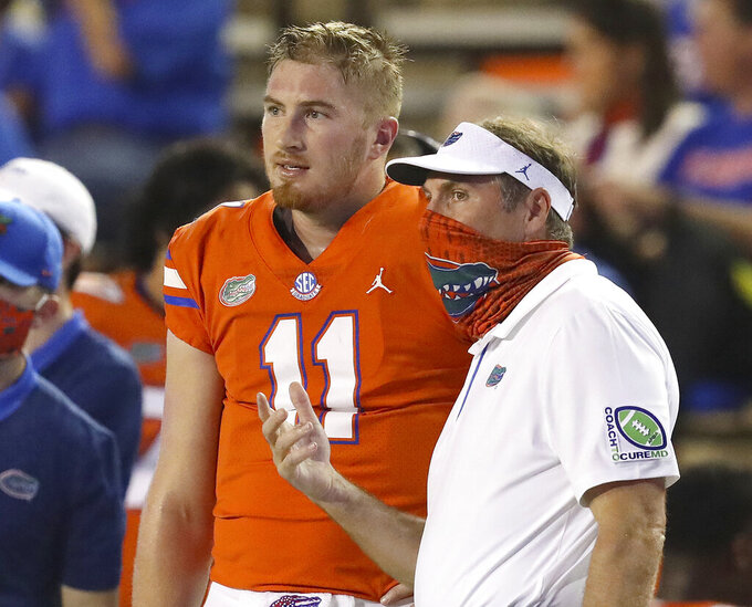 Florida coach Dan Mullen talks with quarterback Kyle Trask  on the sideline during the team's NCAA college football game against Arkansas in Gainesville, Fla., Saturday, Nov. 14, 2020. (Brad McClenny/The Gainesville Sun via AP)