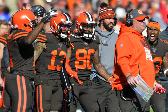 FILE - In this Sunday, Oct. 13, 2019, file photo, Cleveland Browns players encourage head coach Freddie Kitchens to throw a challenge flag during an NFL football game against the Seattle Seahawks, in Cleveland. Being a rookie head coach in the NFL is challenging enough, and also calling plays for the offense only increases the difficulty. Kitchens is finding himself criticized and second-guessed for trying to do too much halfway through his first season. (AP Photo/David Richard, File)