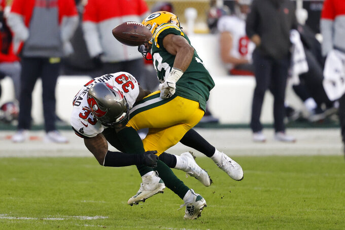 Green Bay Packers' Aaron Jones (33) fumbles after being hit by Tampa Bay Buccaneers' Jordan Whitehead (33) during the second half of the NFC championship NFL football game in Green Bay, Wis., Sunday, Jan. 24, 2021. (AP Photo/Jeffrey Phelps)