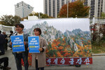 FILE - In this Oct. 28, 2019, file photo, South Korean protesters pose in front of an image of North Korea's Diamond Mountain during a rally, calling for the resumption of Diamond Mountain tourism in Seoul, South Korea. South Korea said Wednesday, Nov. 6, 2019 it offered to send a delegation to check on facilities at a long-stalled joint tourist resort in North Korea. The signs held by the pretster read:
