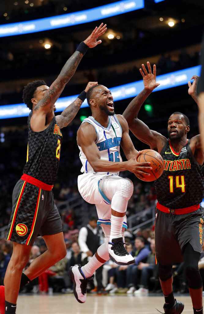 Charlotte Hornets guard Kemba Walker (15) goes between Atlanta Hawks' John Collins (20) and Dewayne Dedmon (14) during the second half of an NBA basketball Saturday, Feb. 9, 2019, in Atlanta. Charlotte won 129-120. (AP Photo/John Bazemore)