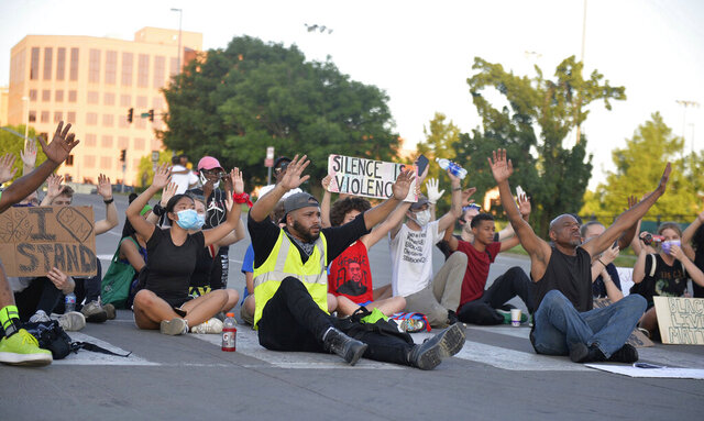 Demonstrations over the death of George Floyd continue, as protesters sit in the street of the Country Club Plaza on Thursday, June 4, 2020, in Kansas City, Mo. (Kylie Graham/The Kansas City Star via AP)