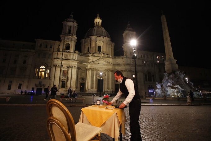 In this Oct. 23, 2020 file photo, a waiter clears a table at a cafe in Piazza Navona Square before the start of a curfew. In times when a pandemic unleashes death and poverty, the concept of what is essential to keep society functioning in a lockdown is gripping Europe. What may stay open in one country may be designated as non-essential just across the border. (AP Photo/Alessandra Tarantino, File)