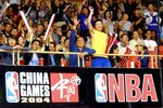 FILE - In this Oct. 14, 2004, file photo, Chinese fans greet players of Houston Rokets and Sacramento Kings during their NBA preseason game in Shanghai, China. (AP Photo/Eugene Hoshiko, File)