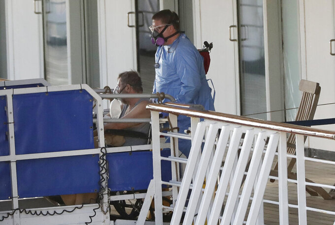 A person in a wheelchair is taken off the cruise ship Rotterdam at Port Everglades, Thursday, April 2, 2020, in Fort Lauderdale, Fla. A cruise ship that has been floating at sea with coronavirus patients aboard for two weeks after being turned away from South American ports was finally allowed to dock in Florida. The Zaandam and a sister ship sent to help it, the Rotterdam, were both given permission to disembark passengers at Port Everglades after days of negotiation with local officials who feared it would divert needed resources from a region that has seen a spike in virus cases. (AP Photo/Wilfredo Lee)