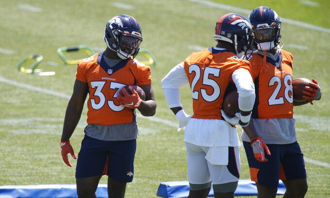 From left, Denver Broncos running backs Javonte Williams, Melvin Gordon and Royce Freeman confer as they takes part in drills during a mandatory minicamp at the NFL team's training headquarters Tuesday, June 15, 2021, in Englewood, Colo. (AP Photo/David Zalubowski)