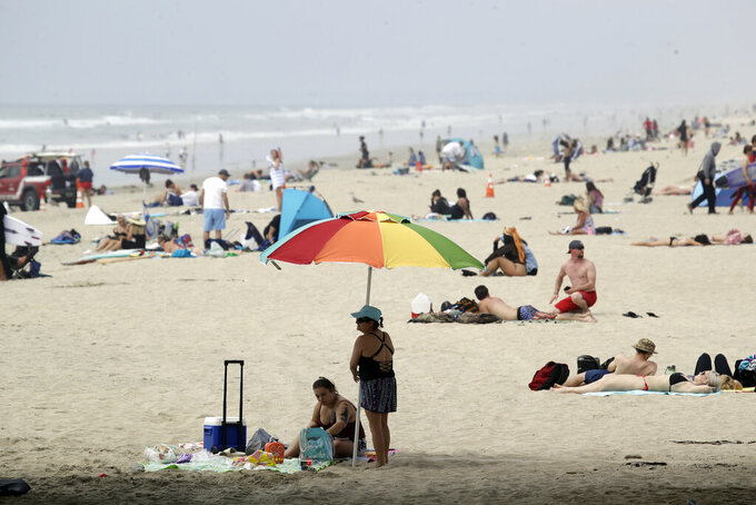 FILE - In this April 30, 2020 photo people crowd the beach in Huntington Beach, Calif. California Gov. Gavin Newsom's administration gave approval Tuesday, May 5, to plans by Huntington Beach and two smaller cities to reopen beaches that fell under his order shutting down the entire Orange County coast after a heat wave drew large crowds to the shore. (AP Photo/Marcio Jose Sanchez, File)