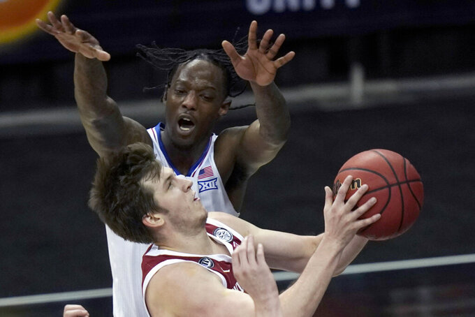 Oklahoma guard Austin Reaves, bottom, shoots while covered by Kansas guard Marcus Garrett, top, during the second half of an NCAA college basketball game in the quarterfinal round of the Big 12 men's tournament in Kansas City, Mo., Thursday, March 11, 2021. Kansas defeated Oklahoma 69-62. (AP Photo/Orlin Wagner)