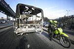 Police ride past a bus that was set on fire during overnight protests triggered by the death of a man who was detained by police for violating social distancing rules to curb the spread of the coronavirus in Bogota, Thursday, Sept. 10, 2020. Javier Ordonez died in a hospital after receiving repeated electric shocks with a stun gun from officers who detained him, seen on a video taken by Ordonez's friend, and published on social media. Authorities announced that the police involved were relieved of their duties as an investigation opens. (AP Photo/Fernando Vergara)