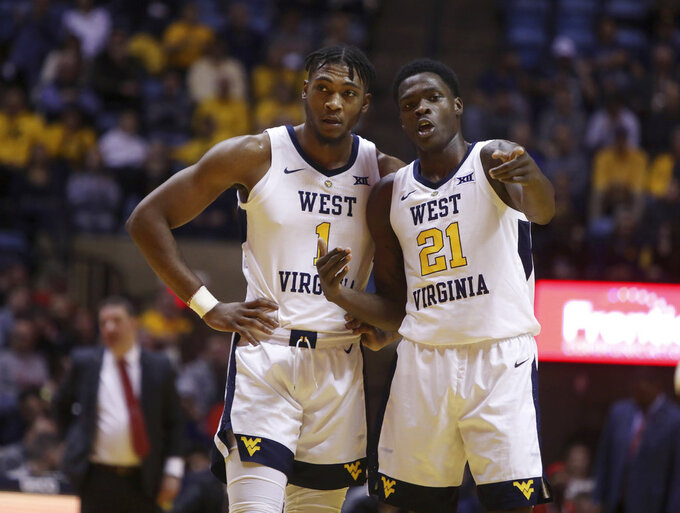 West Virginia forward Derek Culver (1) and forward Wesley Harris (21) go over a play during the second half of an NCAA college basketball game against Texas Tech Wednesday, Jan. 2, 2019, in Morgantown, W.Va. Texas Tech defeated West Virginia 62-59. (AP Photo/Raymond Thompson)