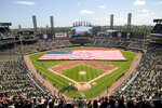 FILE - In this July 4, 2019, file photo, an American Flag is unfurled in the outfield during the playing of the National Anthem before the start a baseball game between the Chicago White Sox and the Detroit Tigers in Chicago. Major League Baseball owners gave the go-ahead Monday, May 11, 2020, to making a proposal to the players' union that could lead to the coronavirus-delayed season starting around the Fourth of July weekend in ballparks without fans, a plan that envisioned expanding the designated hitter to the National League for 2020.  (AP Photo/Mark Black, File)