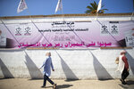 People walk past electoral banners in Rabat, Morocco, Thursday, Sept. 2, 2021, days before the upcoming legislative and regional elections. Millions of Moroccans head to the polls on Sept. 8 to cast ballots in pivotal legislative and regional elections amid strict safety guidelines as the north African country is grappling with a new wave of COVID-19, driven mainly by the Delta variant. (AP Photo/Mosa'ab Elshamy)