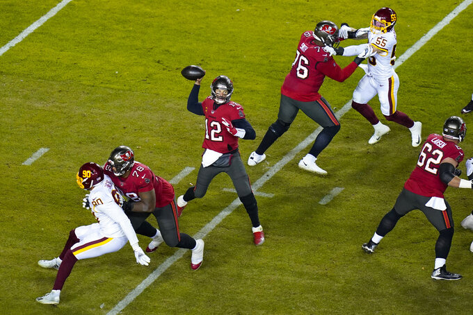 Tampa Bay Buccaneers quarterback Tom Brady (12) throws a pass during the second half of an NFL wild-card playoff football game between the Tampa Bay Buccaneers, and Washington Football Team, Saturday, Jan. 9, 2021, in Landover, Md. Tampa Bay won 31-23. (AP Photo/Al Drago)