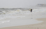 A surfer comes back in from surfing the high waves in Mexico Beach, Fla., after Tropical Storm Nestor hit the town on Saturday, Oct. 19, 2019.   Nestor was downgraded Saturday after it spawned a tornado that damaged homes and a school in central Florida but spared an area of the Panhandle devastated one year ago by Hurricane Michael.  (Joshua Boucher/News Herald via AP)